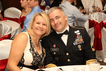 military man smiling with wife
