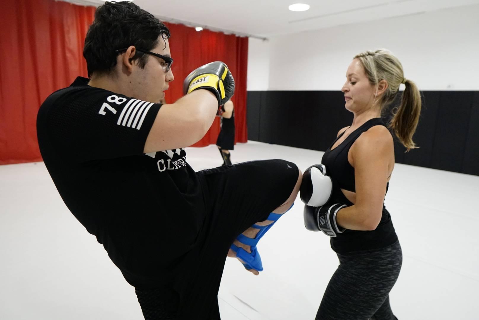 man and woman practicing muay thai kicks
