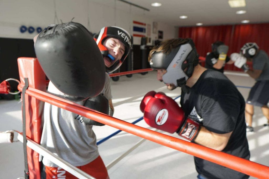 two men sparring in ring, glove punching at camera