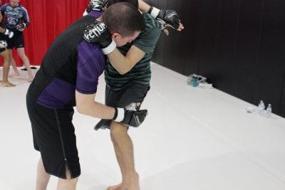 man in purple shirt and man in green striped shirt practising jiu-jitsu