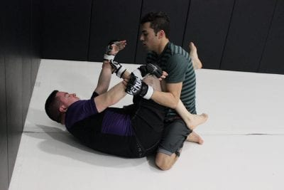 men learning grappling techniques on mat