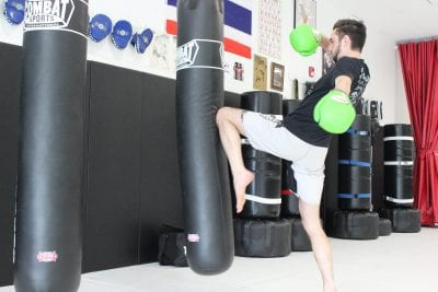 man in green gloves in light room kicking a heavy bag