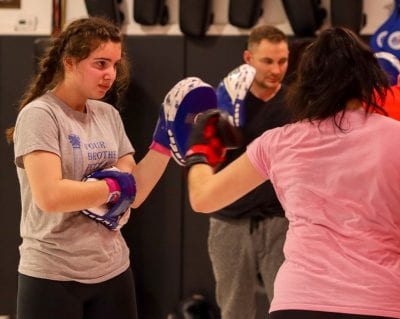 woman holding focus mitts for another woman