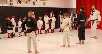kids lined up and participating in bjj class