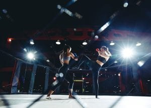 two women mma fighting in ring